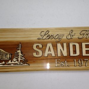 Redwood sign with cabin and evergreen trees surrounding cabin with husband and wife name and marriage date