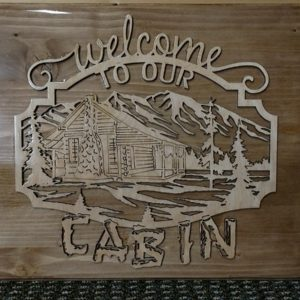 Welcome to our cabin wooden sign, with mountains in back ground